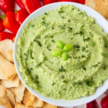 Edamame hummus with peppers, pita chips, and radishes