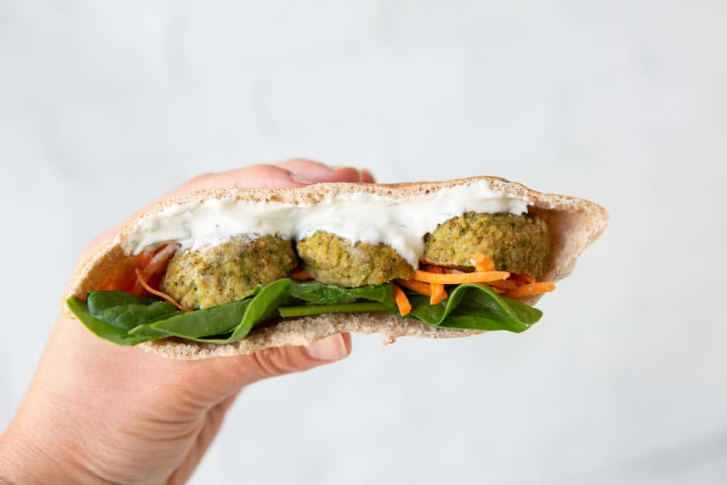 healthy hacks for plant based eating - Whole wheat pita with meatballs, sauce, spinach, and carrots
