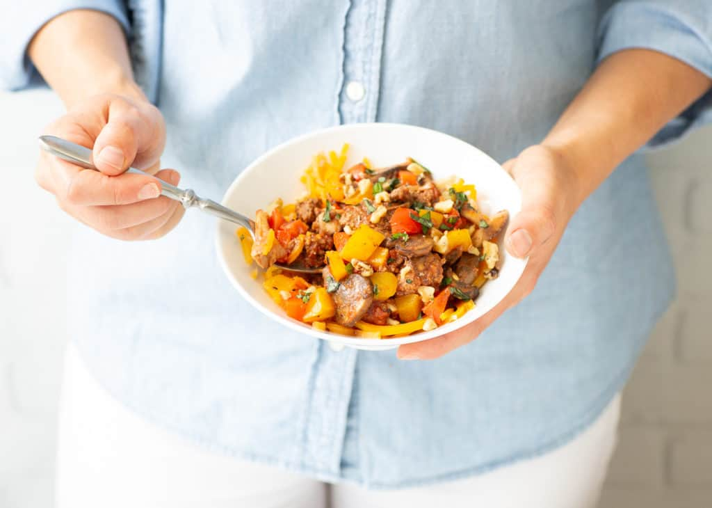 woman holding bowl of healthy beef veggie skillet